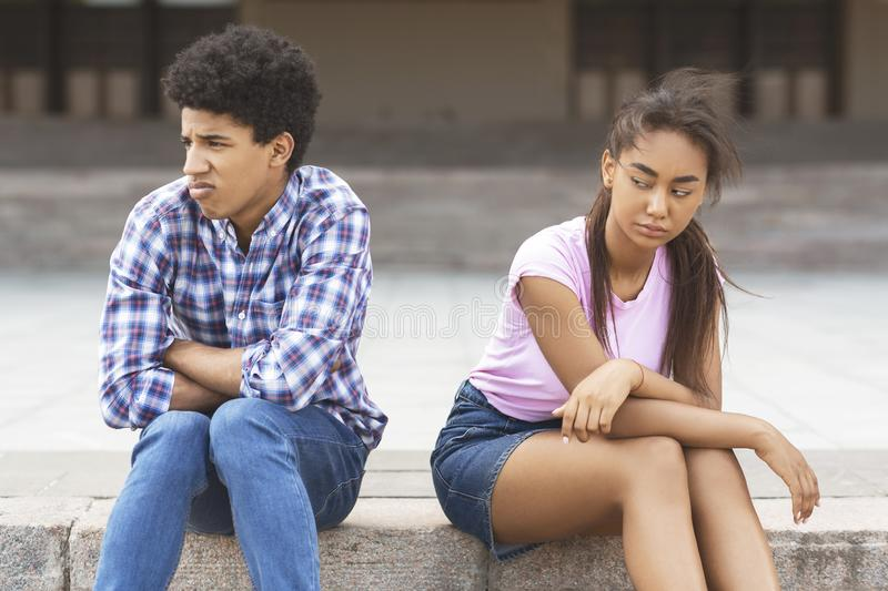 Offended teen couple sitting outdoors, ignoring each other stock photo