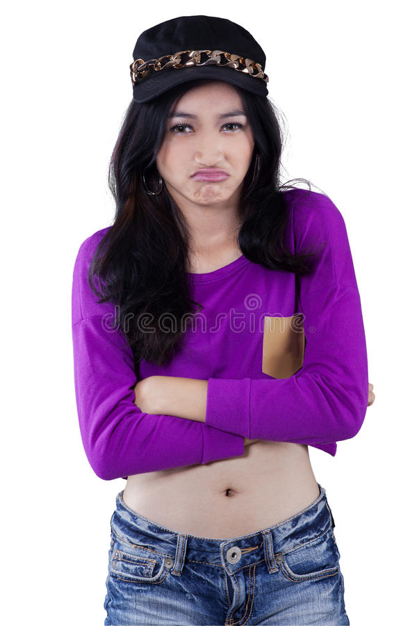 Offended teenage girl in studio. Portrait of modern teenage girl standing in the studio with offended face expression royalty free stock image