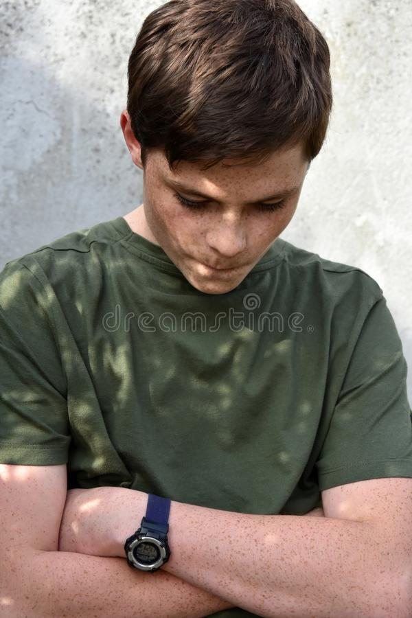 Offended and thoughtful looking teenage boy stock photo