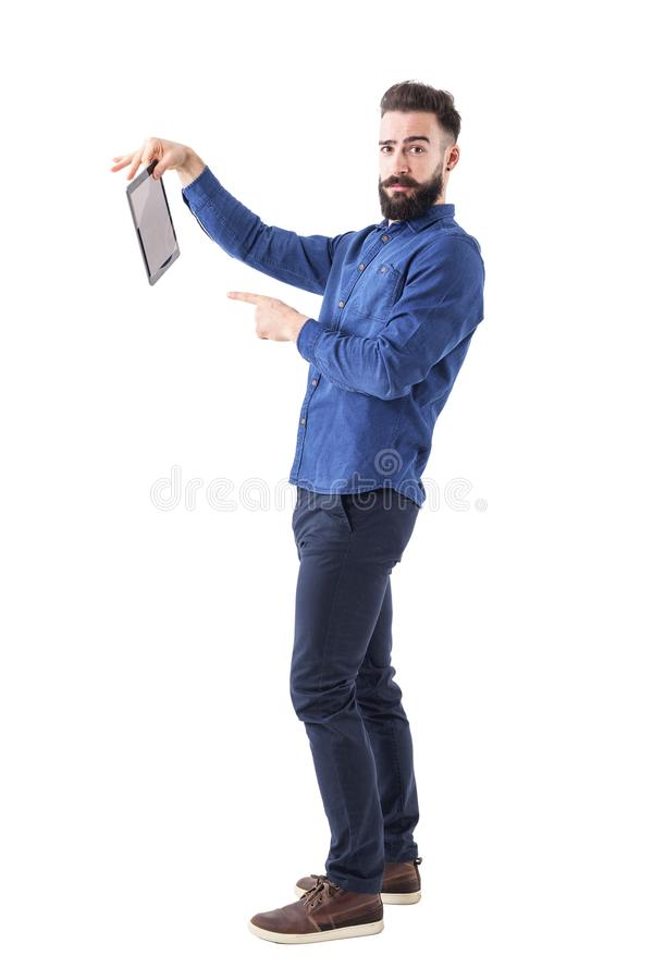 Offended young businessman holding and pointing finger at tablet computer looking at camera. Full body isolated on white background stock images