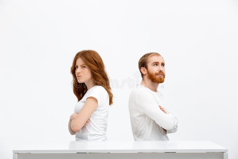 Offendi la ragazza ed il ragazzo della testarossa che si siedono allo scrittorio bianco fotografia stock libera da diritti