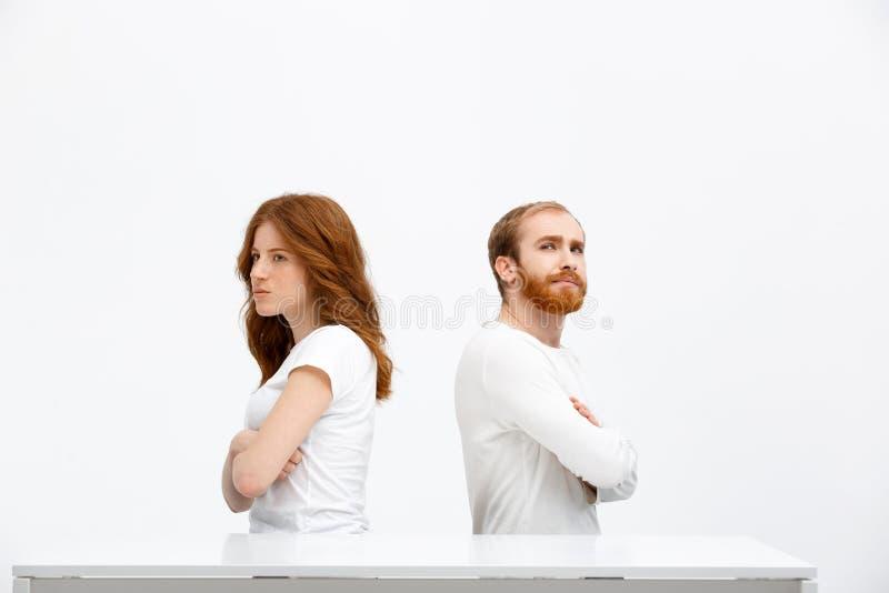 Offendi la ragazza ed il ragazzo della testarossa che si siedono allo scrittorio bianco immagine stock libera da diritti