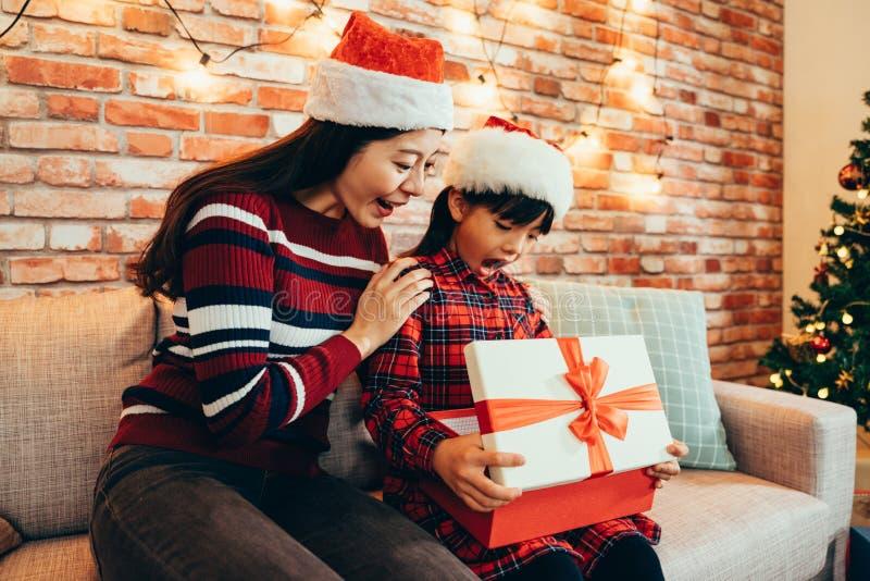 Offene Geschenkbox der Frau und des kleinen Mädchens am 26. Dezember lizenzfreie stockbilder