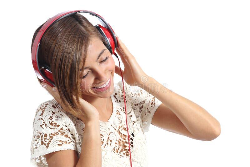 Offene glückliche Frau, die der Musik von den roten Kopfhörern glaubt stockfotos
