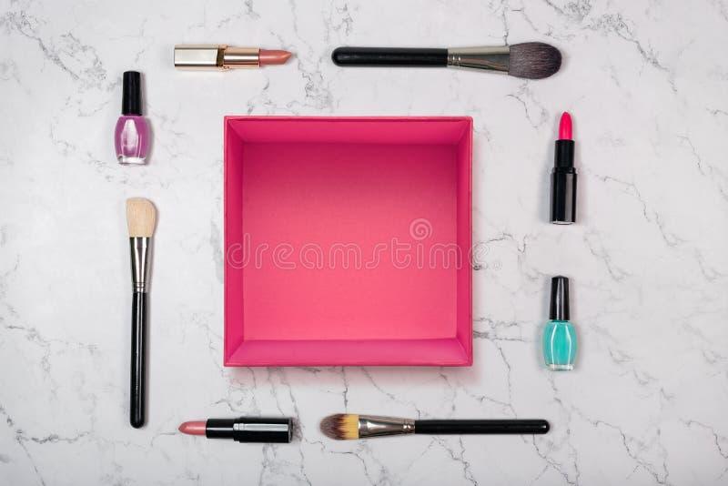 Offene rosa Geschenkbox mit Make-upbürsten und dekorativen Kosmetik auf natürlichem Marmorhintergrund stockfoto