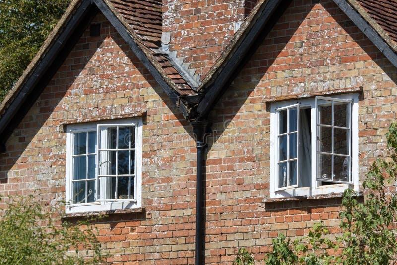 Offene Schiebefenster auf einem klassischen englischen Landhäuschenhaus lizenzfreies stockfoto