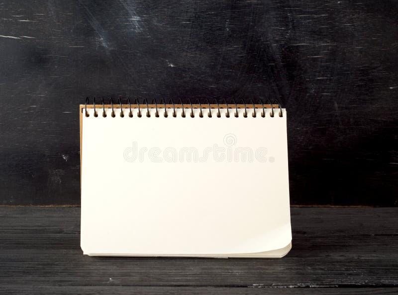 offene Spiralplatte mit weißen Blechen auf schwarzer Kreideplatte stockfotos