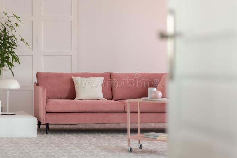 Offene T?r zum modernen Wohnzimmer mit wei?er Wand und rosa PastellSofa stockfotos