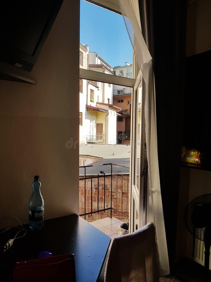 Offene Tür zur Balkon Ansicht des kleinen Südraumes Hof des Patios im sonnigen Wetter des Schattens außerhalb des Fensters stockfotografie