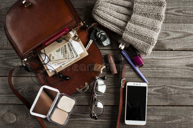 Offene Tasche Browns mit verschiedenem weiblichem Zubehör stockfoto