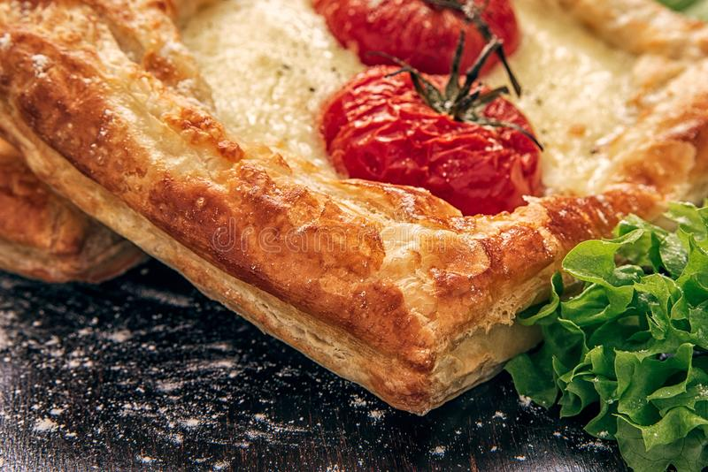 Offene Torte vom Blätterteig mit Käse und Tomaten mit Kopfsalatblättern stockfoto