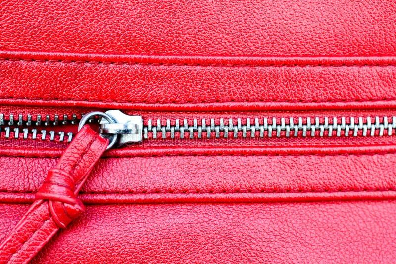Offener Abschluss des Reißverschlusses teils herauf Detailfoto auf einem roten ledernen Beschaffenheitshintergrund stockfoto