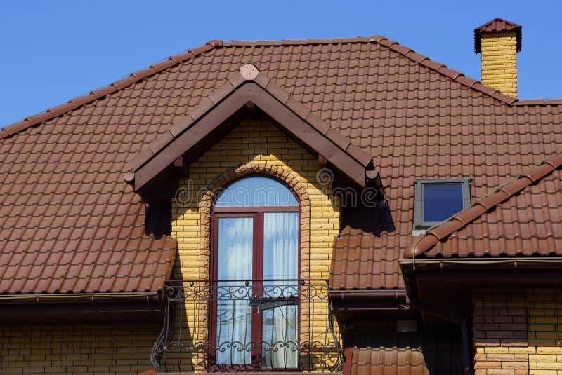 Offener Balkon auf der Backsteinmauer des Hauses unter dem braunen mit Ziegeln gedeckten Dach gegen den Himmel stockfotografie