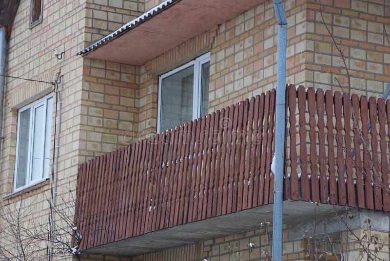 Offener brauner hölzerner Balkon von Planken und von Fenster auf Backsteinmauer lizenzfreie stockfotos