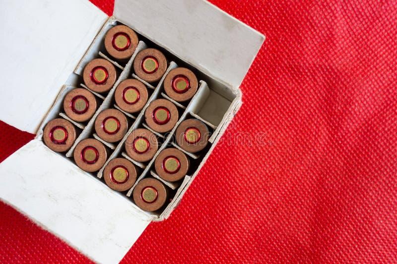 Offener Kasten Gewehrpatronen auf rotem Hintergrund Eine Zelle ist als Konzept der benutzten Kugel leer Nahaufnahmebild der Munit lizenzfreie stockbilder
