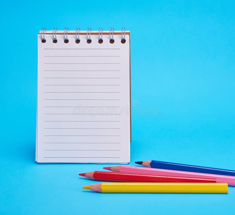Offener leerer Notizblock in der Linie und in den mehrfarbigen hölzernen Bleistiften stockfotografie