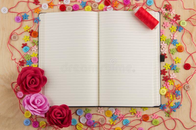 Offener Notizbuchseite Needlewoman mit Knöpfen, Thread, Blumen und stockfoto