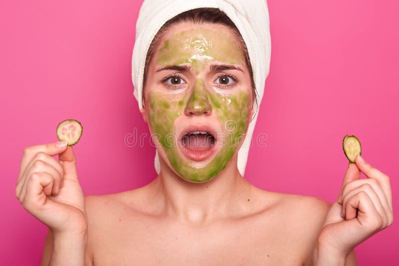Offener Schuss der überraschten reizenden jungen Frau hält Kiefer fallen gelassen, betrachtet im Spiegel, entsetzt, um grüne Mask lizenzfreies stockfoto