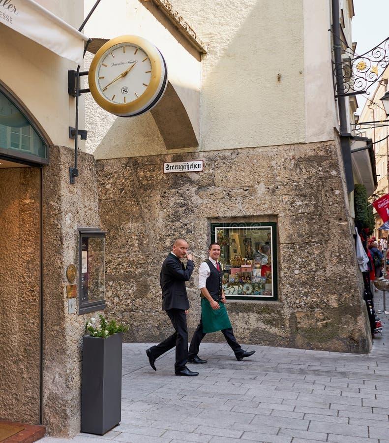 Offener Schuss von zwei Geschäftsleuten, die in Salzburg, Österreich gehen lizenzfreies stockfoto