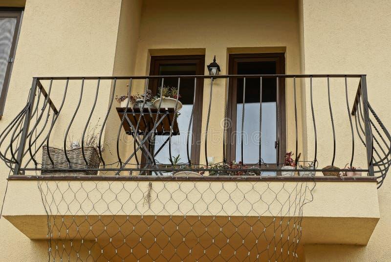 Offener schwarzer Eisenbalkon auf einer braunen Wand mit Fenstern lizenzfreie stockfotografie