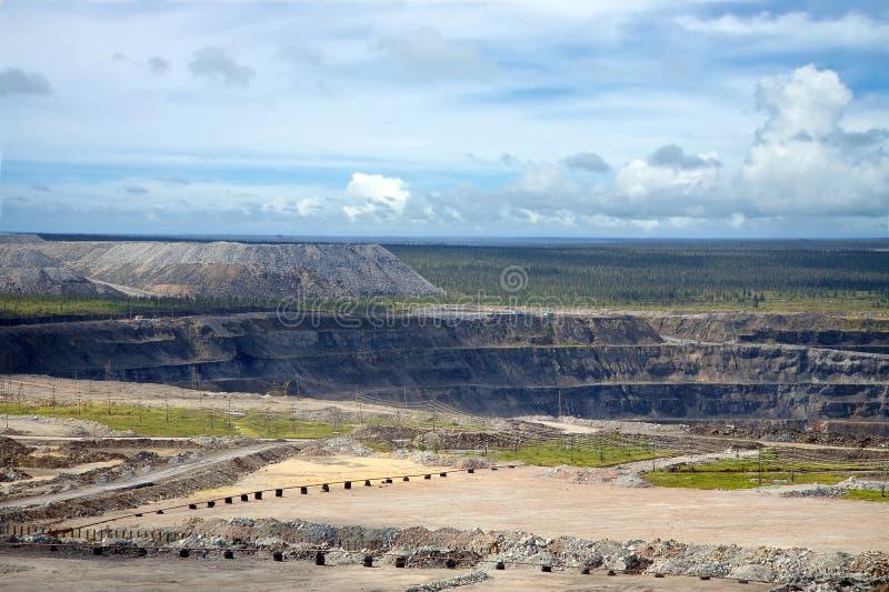 Offenes Bergwerk des Diamanten umgeben durch ettles und industrielles Feld lizenzfreie stockfotos