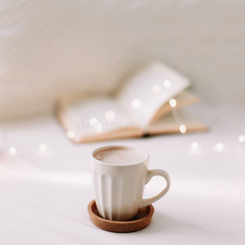 Offenes Buch auf Bedsheets und einem Tasse Kaffee Guten Morgen Fr?hst?ckszeit Fr?hst?ck im Bett Flache Lage lizenzfreie stockfotos