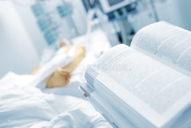 Offenes Buch auf dem Hintergrund des geduldigen Betts Symbol von medica stockfoto