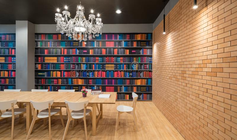 Offenes Buch auf einer hölzernen Plattformtabelle mit Holzstühle und niemand in einem modernen Bibliothekshintergrund lizenzfreies stockbild