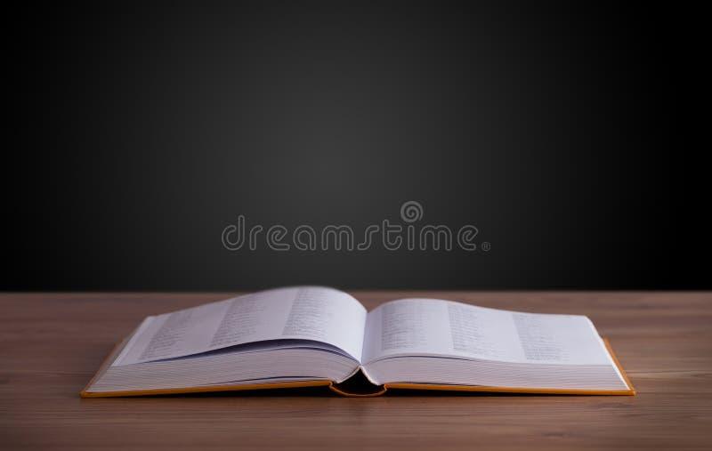Offenes Buch auf hölzerner Plattform stockfotos
