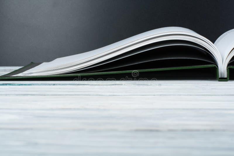 Offenes Buch auf hölzerner Plattformtabelle und schwarzem Bretthintergrund Zurück zu Schule Bildungskonzept mit Kopienraum für Ih stockbilder