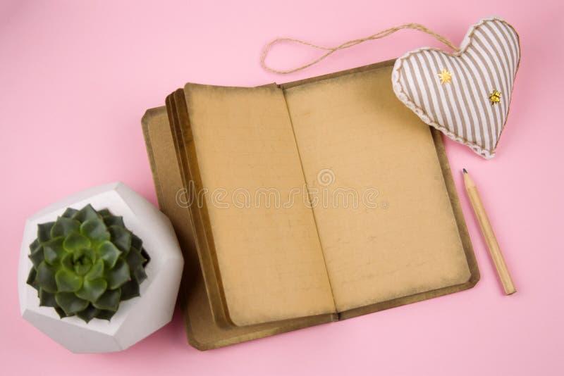 offenes Buch mit antikem Papier, weichem Spielzeug in einer Form des Herzens, Bleistift und saftigem lizenzfreie stockbilder
