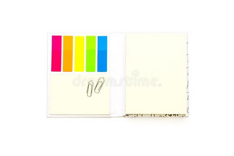 Offenes Buch mit Farbzeckenanmerkungen und -Büroklammern lizenzfreie stockfotos