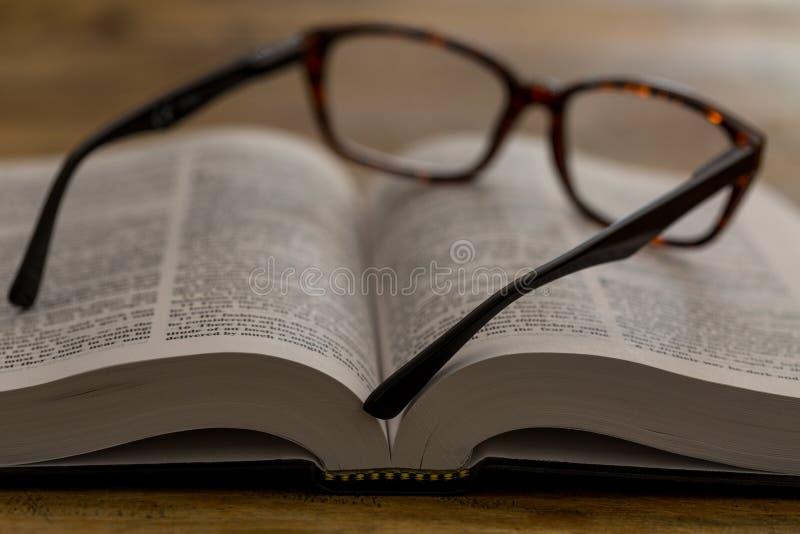 Offenes Buch mit Gläsern auf hölzernem Schreibtisch, Nahaufnahme stockfotos
