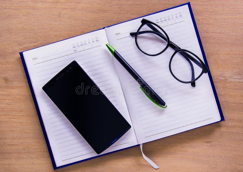 Offenes Buch mit intelligentem Telefon- und Briefpapierschreibtisch stockfotos