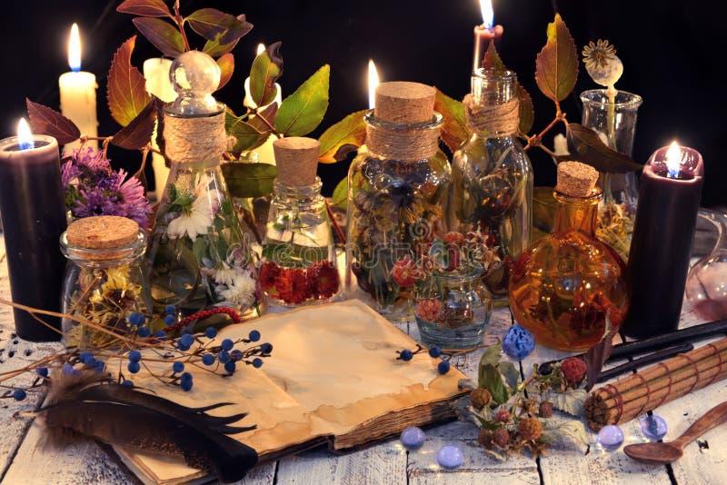 Offenes Buch mit Kopienraum, Kräuter und Beeren, schwarze Kerze und magische Gegenstände auf Hexentabelle lizenzfreie stockfotos