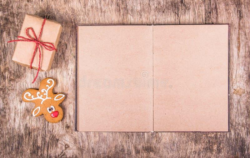 Offenes Buch mit leeren Seiten, Lebkuchen und einem Geschenk Neues Jahr ` s und Weihnachten Hintergründe und Beschaffenheiten lizenzfreie stockbilder