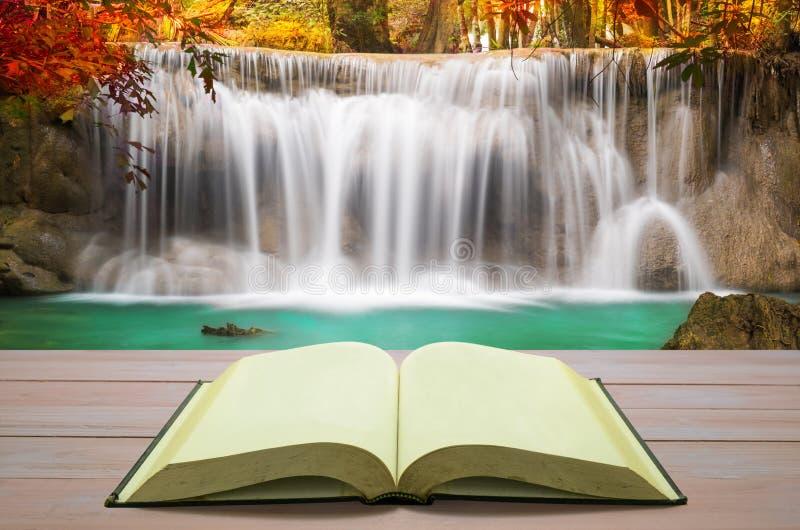 Offenes Buch mit schönem Herbstwasserfall im tiefen Wald-backgro lizenzfreies stockbild