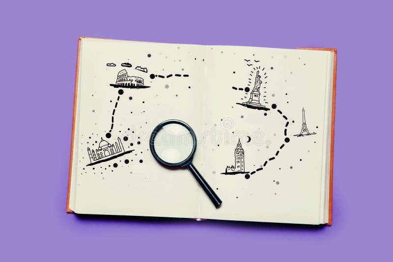 Offenes Buch mit Vergrößerungsglas und Karte der Reise stockbilder