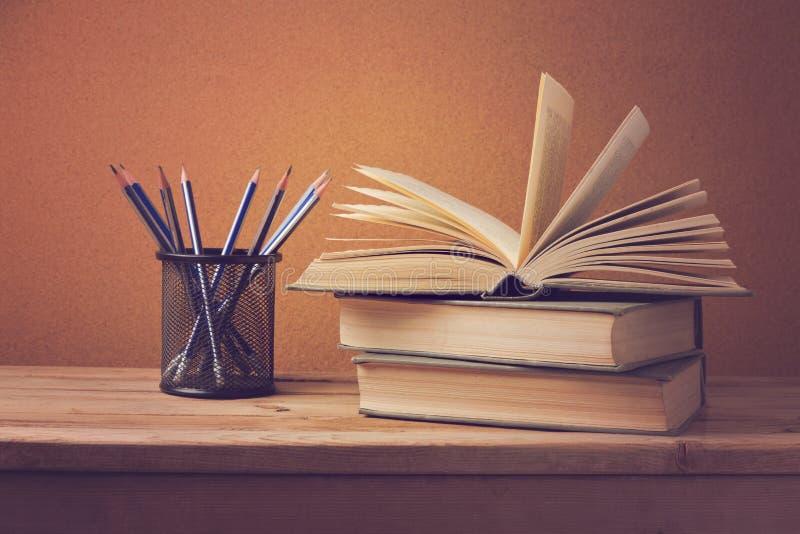 Offenes Buch und Bleistifte auf hölzerner Plattformtabelle stockbild