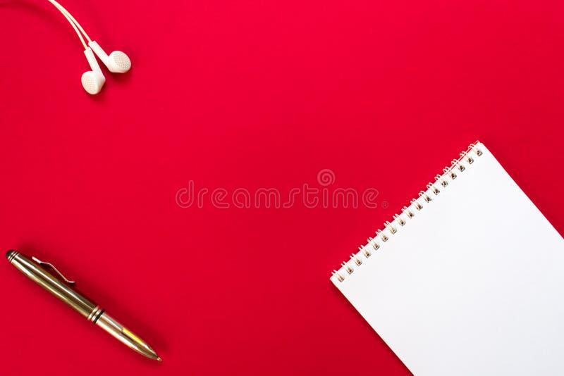 Offenes leeres Notizbuch, Kopfhörer und Stift der Draufsicht auf rotem Tabellenhintergrund stockfotos