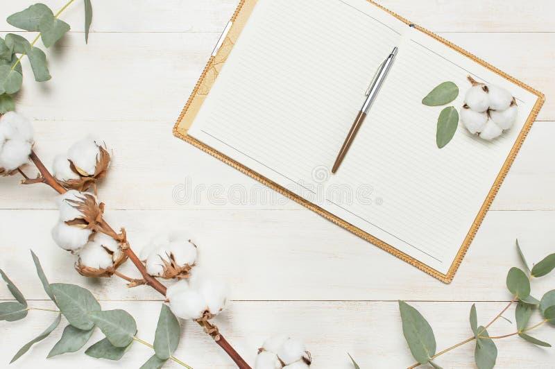 Offenes Notizbuch mit Leerseiten, Stift, dem Eukalyptuszweig und den Baumwollblumen auf weißer hölzerner flacher Lage der Draufsi lizenzfreie stockfotografie