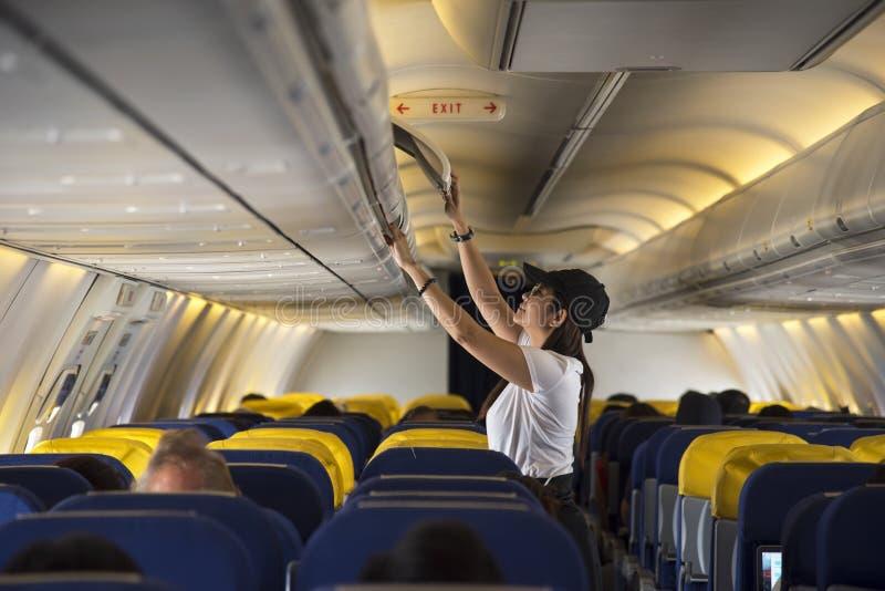 Offenes obenliegendes Schließfach der Reisendfrau auf Flugzeug lizenzfreie stockbilder