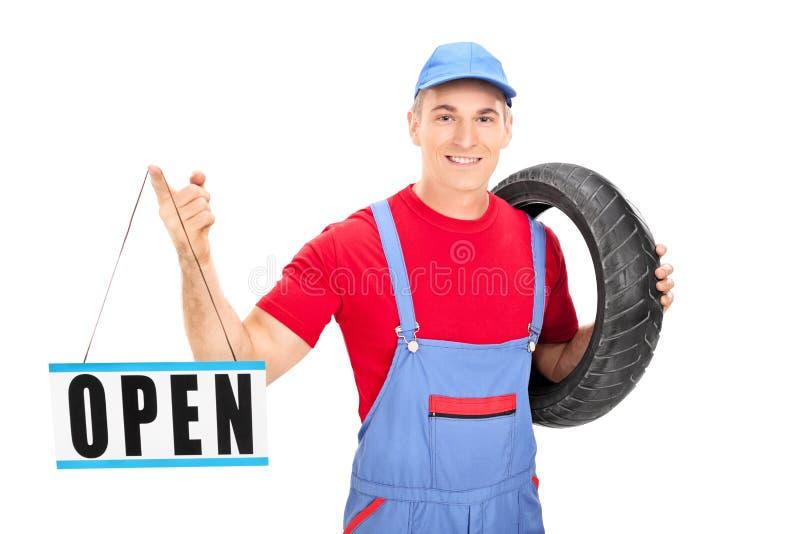 Offenes Zeichen der jungen männlichen Mechanikerholding lizenzfreie stockbilder