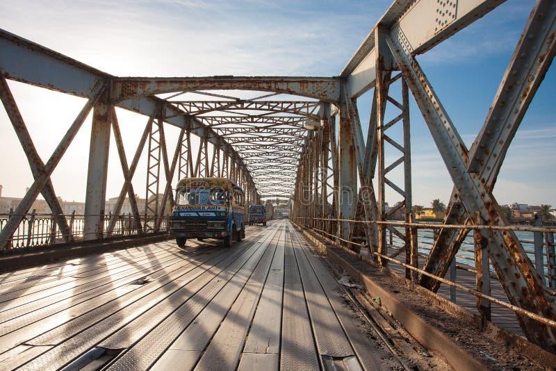 Offentlig buss som korsar den Faidherbe bron i Saint Louis fotografering för bildbyråer