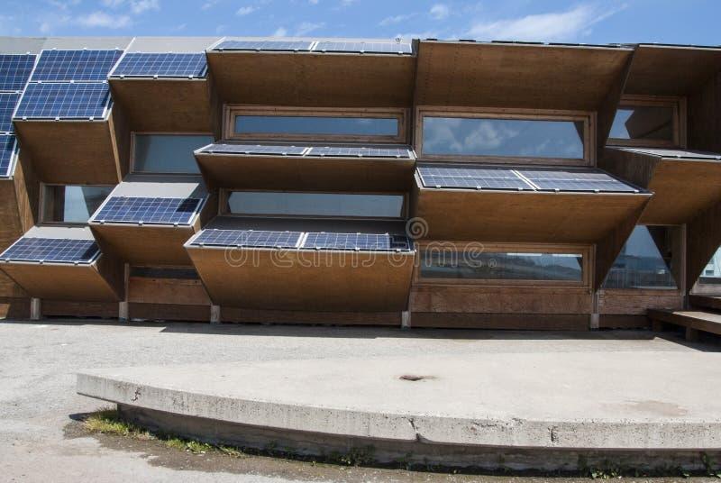 Offentlig byggnad som göras av solpanel-, trä- och spegelexponeringsglas fotografering för bildbyråer