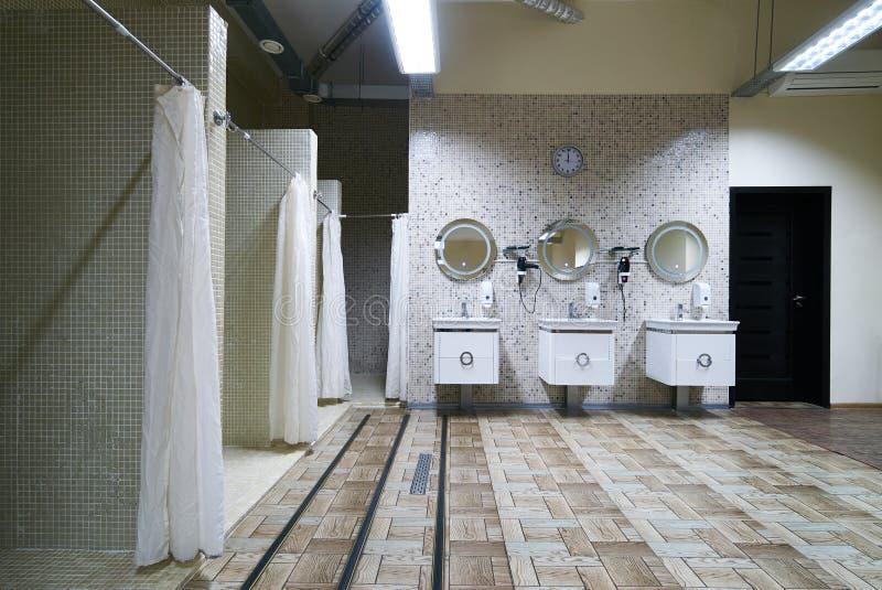 Offentlig duschinre med everal duschar arkivbild
