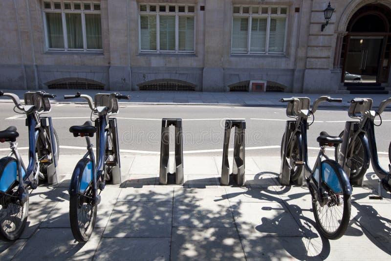 Offentlig hyra cyklar i en linje, London, UK arkivfoto