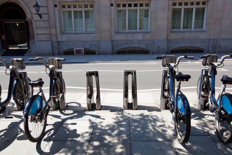 Offentlig hyra cyklar i en linje, London, UK royaltyfri foto