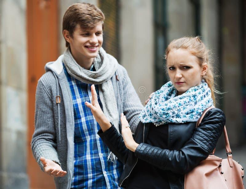 Offentlig mobbning: man som jagar den irriterade flickan fotografering för bildbyråer