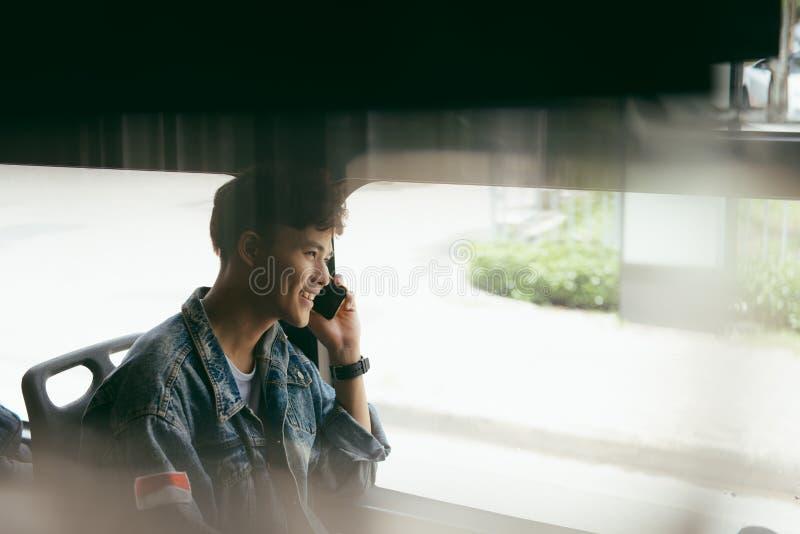 offentlig transport Folk i bussen Asiatisk man som talar på cell P royaltyfria foton